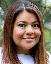 A photograph of Alex Hernandez-Castro, a Latina smiling at the camera