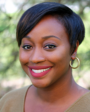 A photograph of Tamra Gibson, a Black woman wearing a tan shirt who is smiling at the camera while standing in front of an evergreen background