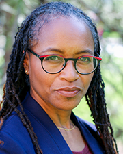 A photograph of Kimberly Morgan, a Black woman wearing a dark blue blazer standing in front of an evergreen background