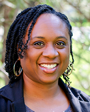 A photograph of Korri Thompson, a Black woman wearing a black blazer smiling at the camera