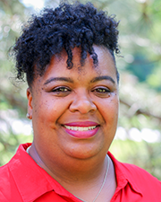 A photograph of Verneta White, a Black woman wearing a red polo smiling at the camera