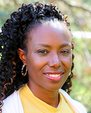 A photograph of LaCretia Wooten, a black woman wearing a yellow shirt with white cardigan smiling at the camera